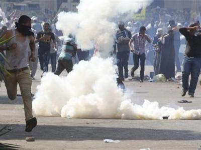 Un grupo de partidarios del ex presidente egipcio Mohamed Mursi huye de gases lacrimógenos arrojados por fuerzas de la policía en El Cairo, jul 5 2013
