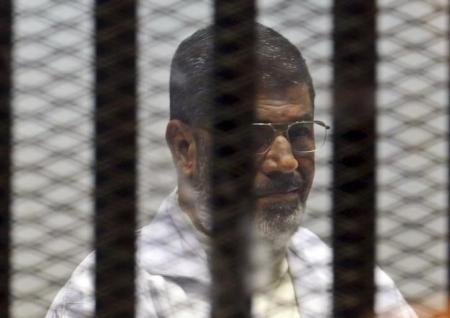En la imagen de archivo, Mohamed Murs sentado detrás de unos barrotes con otros miembros de Hermanos Musulmanes en la crote a las afueras de El Cairo