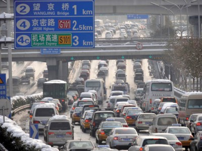Vehicles make their way along a street after a heavy snowfall in Beijing on November 10, 2009. Despite a massive effort to clear the capital of snow that involved over 15,000 workers, many roads remained blocked, as Chinese scientists artificially induced the second major snowstorm to wreak havoc in Beijing this season, state media said, reigniting debate over the practice of tinkering with Mother Nature.  CHINA OUT AFP PHOTO (Photo credit should read STR/AFP/Getty Images)