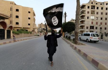 Imagen de archivo de un partidario del Estado Islámico ondeando una bandera del grupo en Raqqa, Siria, jun 29 2014. El Ministerio de Defensa de Irak anunció el miércoles la muerte del segundo miembro más importante de Estado Islámico (EI) en un ataque aéreo de la coalición sobre una mezquita del norte del país, en la que estaba reunido con otros militantes. REUTERS/Stringer