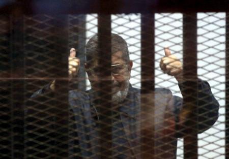 El depuesto presidente egipcio Mohamed Mursi es visto detrás de las rejas durante su juicio en una corte en El Cairo, 30 de abril de 2015. Un tribunal egipcio pidió el sábado la pena de muerte para el ex presidente Mohamed Mursi y más de 100 miembros de los Hermanos Musulmanes en relación con una fuga de presos masiva en 2011. REUTERS/Al Youm Al Saabi Newspaper/Files