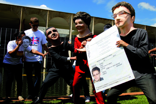 Members of the Avaaz online community organization stage in front of the Itamaraty Forein Ministry Palace the delivery of the Brazilian passport by Brazilian President Dilma Rousseff to Edward Snowden while U.S. President Barack Obama tries to stop her, in Brasilia, on February 13, 2014. Avaaz members have collected over a million signatures in favor of the asylum application for Snowden, the former CIA technician  that disclosed the spying by the U.S. government to millions of people, among whom President Rousseff and German Chancellor Angela Merkel. AFP PHOTO/Beto BARATA