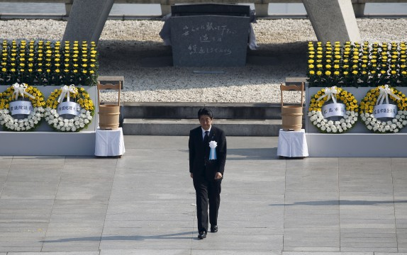 Japan's Prime Minister Shinzo Abe walks as he attends a ceremony at the Peace Memorial Park in Hiroshima, western Japan, August 6, 2015, on the 70th anniversary of the world's first atomic bombing of the city. Japan on Thursday marks the 70th anniversary of the attack on Hiroshima, where the U.S. dropped an atomic bomb on August 6, 1945, killing about 140,000 by the end of the year in a city of 350,000 residents. It was the world's first nuclear attack. The Atomic Bomb Dome, or Genbaku Dome, was the only structure left standing in this district of the city and has been preserved as a peace memorial.   REUTERS/Toru Hanai