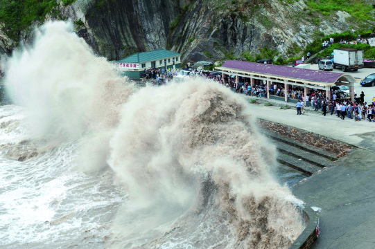 People gather to see huge waves as typhoon Chan-hom comes near Wenling, east China's Zhejiang province on July 10, 2015. Typhoon Chan-hom lashed Japan's Okinawa island chain on July 10 as it pushed towards Taiwan and onto China, leaving more than 20 people injured. CHINA OUT   AFP PHOTO