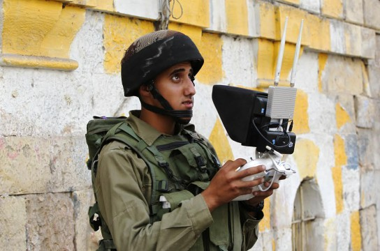 An Israeli soldier uses an unmanned surveillance drone to monitor Palestinian stone throwers in the occupied West Bank city of Hebron as Israeli settlers visit the holy site of the tomb of Atnaeil Ben Kinaz during the celebrations of the Jewish Sukkot holiday or the feast of the Tabernacles, on September 30, 2015. The holiday commemorates the rededication of the holy temple in Jerusalem after the Jews' 165 B.C. victory over the Hellenist Syrians when Antiochus, the Greek King of Syria, outlawed Jewish rituals and ordered the Jews to worship Greek gods. AFP PHOTO / HAZEM BADER