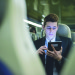 Portrait of young businessman commuter using digital tablet on train.