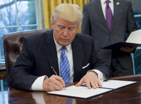 US President Donald Trump signs an executive order withdrawing the US from the Trans-Pacific Partnership in the Oval Office of the White House in Washington, DC, January 23, 2017. Trump the decree Monday that effectively ends US participation in a sweeping trans-Pacific free trade agreement negotiated under former president Barack Obama. / AFP PHOTO / SAUL LOEB